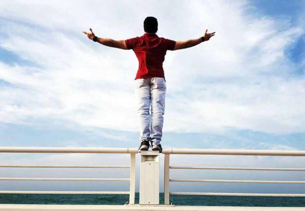 Finanzielle Unabhängigkeit und Freiheit im Check. Bild: https://www.pexels.com/photo/person-raising-hands-mid-air-sidewards-while-standing-on-gray-steel-railings-680257/ Autor: Sanketh Rao